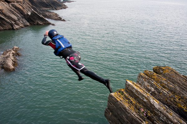 Someone jumping from a cliff ledge into the sea, as part of a coasteering activity